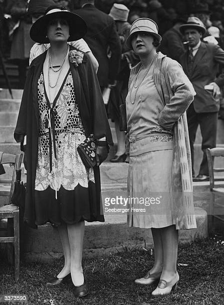 Two outfits designed by Agnes One dress has a lace overbodice a deep vneck over a vest and is worn under a wrapover coat an embroidered clutch bag is...