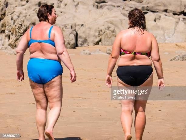 two overweight women in bikinis walking on the beach. caswell bay beach, near swansea, on the gower peninsular, south wales. june - hot women pics stock pictures, royalty-free photos & images