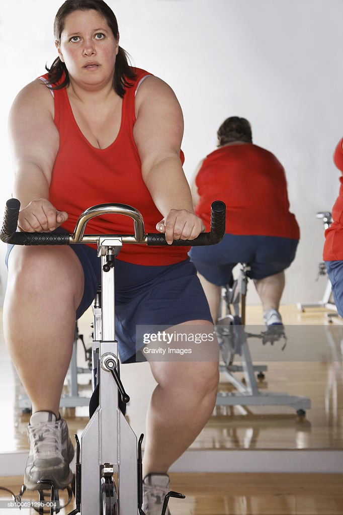 Two overweight women on exercise bike in gym : Stockfoto