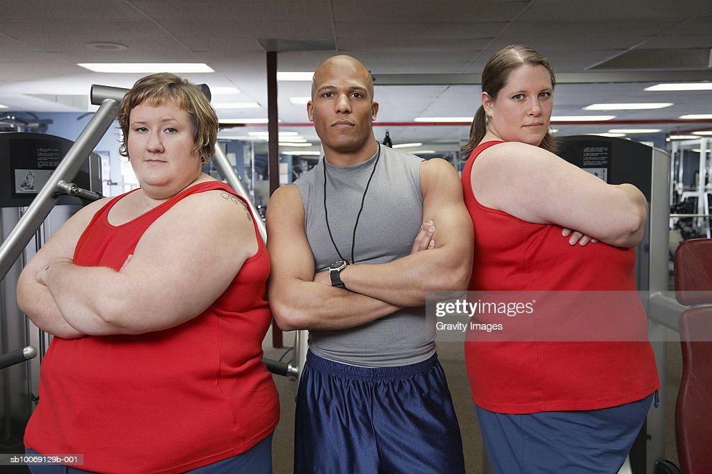 Two overweight women standing with man in gym, portrait : Stockfoto