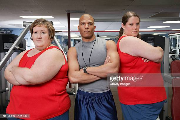 Two overweight women standing with man in gym, portrait
