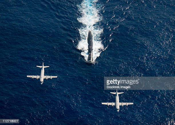 Two P-3 Orion maritime surveillance aircraft fly over attack submarine USS Houston.