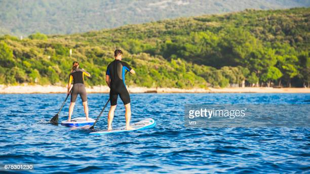 Two paddle boarders rowing towards the coast