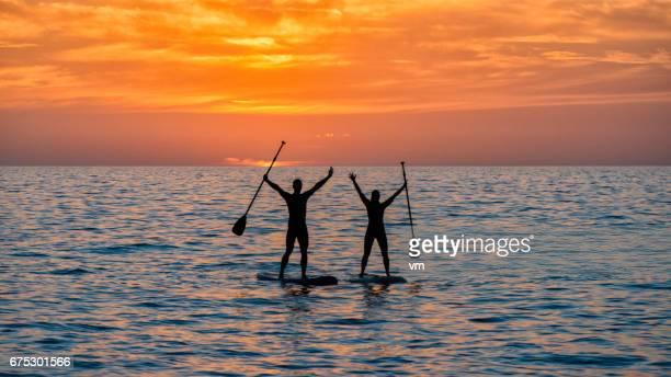 Zwei Paddel Boarder mit erhobenen Armen bei Sonnenuntergang