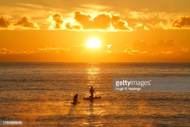 Two paddle-boarders watch the first sunrise of the year at Gyllyngvase Beach on January 1, 2021 in Falmouth, United Kingdom. January 1st 2021 marks...