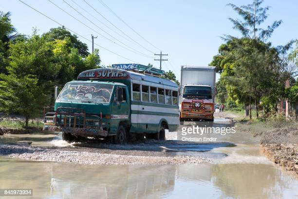 PortauPrince Haiti December 09 2012 Two painted trucks are trying to find their way trough a damaged road with many potholes filled with water