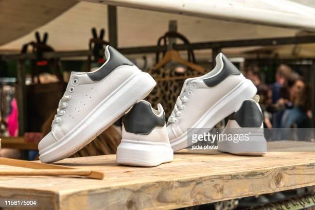 two pair of sport shoe displayed on a wooden board - witte schoen stockfoto's en -beelden