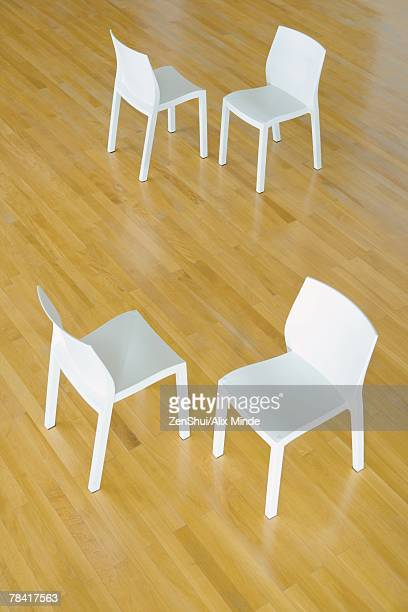 Two pairs of chairs on hardwood floor, high angle view