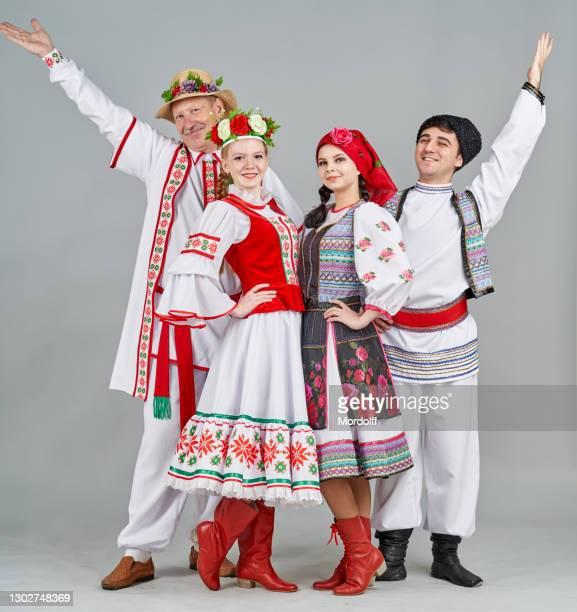 dos pares de bailarines en bielorrusia y moldavia ropa popular están de pie y mirando alegremente a la cámara - moldavia fotografías e imágenes de stock