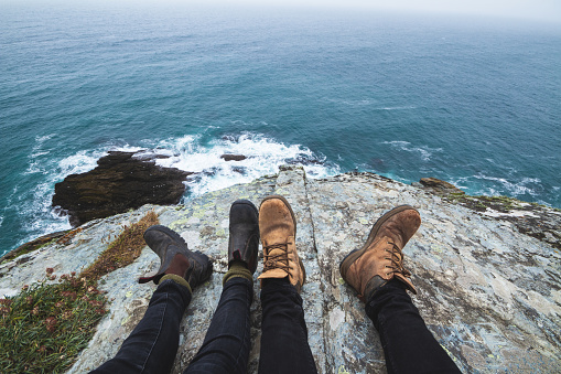 Two Pairs of Feet by a Cliff Overlooking the Sea - gettyimageskorea