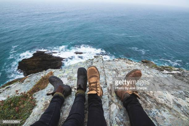 two pairs of feet by a cliff overlooking the sea - womens pretty feet stock pictures, royalty-free photos & images