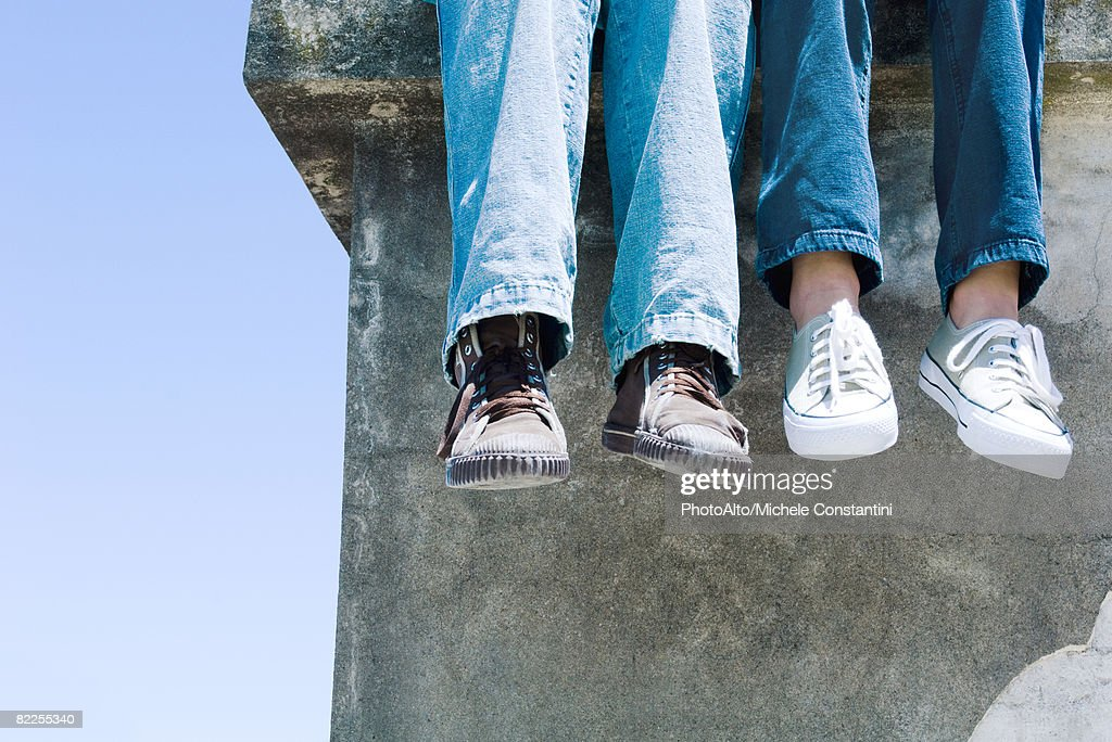 Two pairs of legs dangling over concrete ledge : Stock Photo