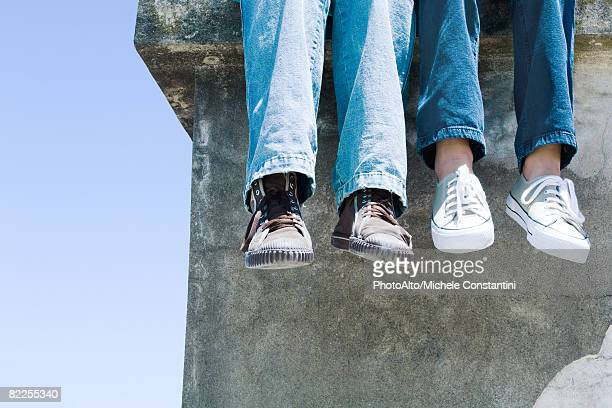 two pairs of legs dangling over concrete ledge - pair stock pictures, royalty-free photos & images