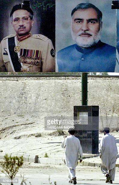 Two Pakistani pedestrians walk under the billboard which displays the portrait of Pakistani President Pervez Musharraf and province NWFP Chief...