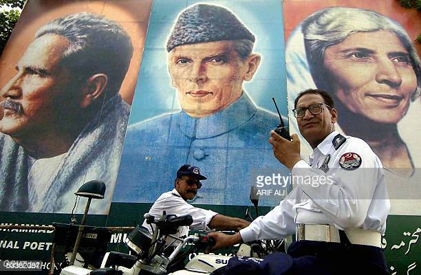 Two Pakistani policemen guard a street standing in front of a portrait of the country's founder Mohammad Ali Jinnah along with his sister Fatima...