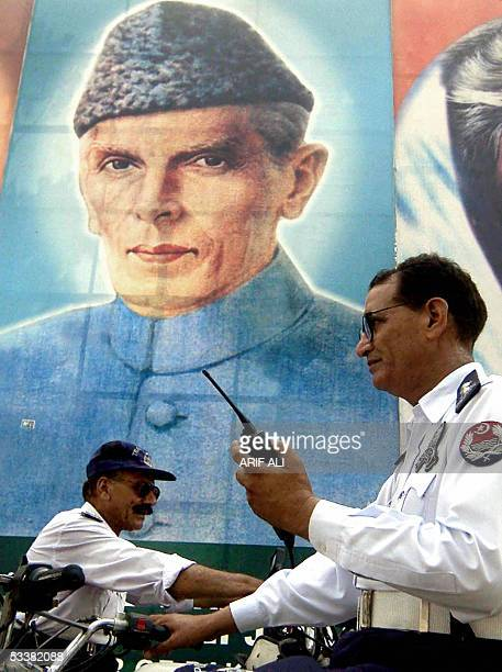 Two Pakistani policemen guard a street standing in front of a portrait of the country's founder Mohammad Ali Jinnah in Lahore, 13 August 2005, a day...