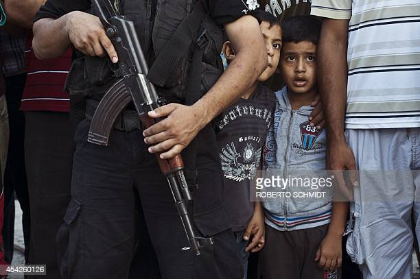 Two Palestinian boys peak from behind a Hamas militant during a Hamas militants parade in Shejaiya on August 27 2014 Israel and Palestinians both...