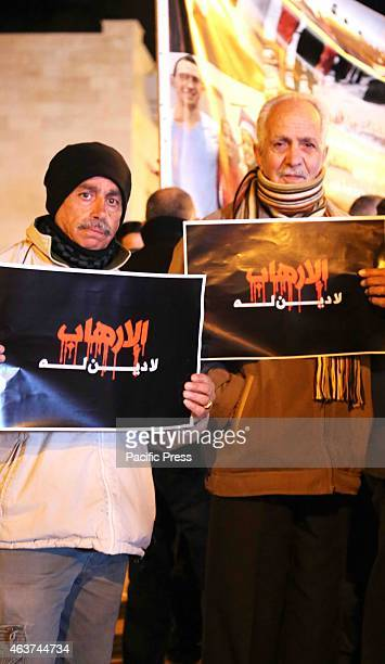 Two Palestinian men hold up posters during a vigil held in the West Bank city of Beit Sahur Following another video released by ISIS on Sunday which...