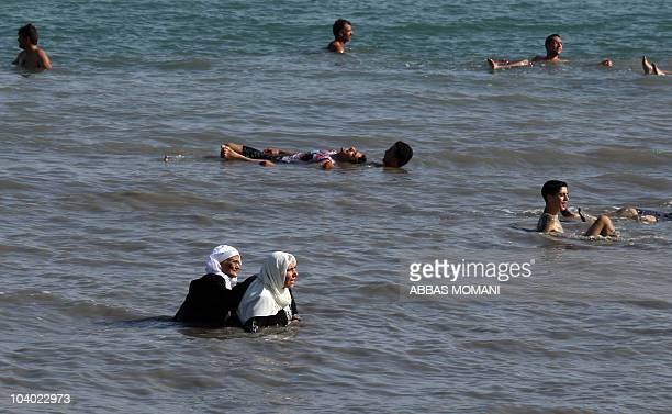 Two Palestinian Muslim women swim in their clothes on September 12 2010 in the waters of the Dead Sea in the West Bank during the Muslim holiday of...