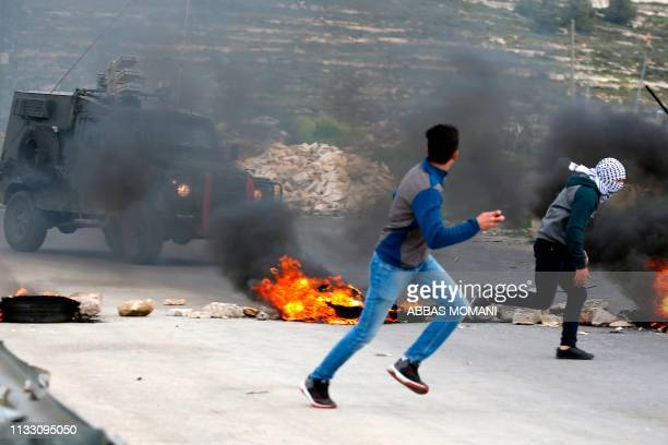 Two Palestinian protesters run for cover during clashes with Israeli forces on the outskirts of Ramallah in the occupied West Bank following a...
