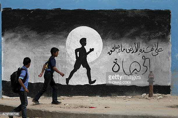 Two Palestinian schoolboys walk past a graffiti painted on a wall of the United Nations school of Beit Hanun in the northern Gaza Strip on May 9 2016...