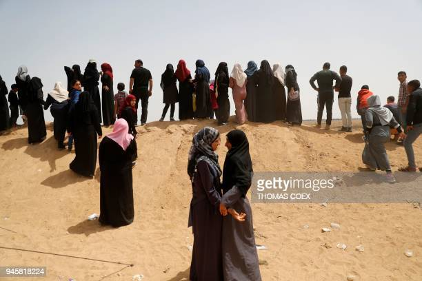 Two Palestinian women hug near the border fence with Israel east of Khan Yunis in the southern Gaza strip on April 13 2018 Several thousand Gazans...