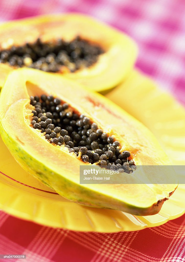 Two papaya halves on yellow plate, close-up : Stockfoto