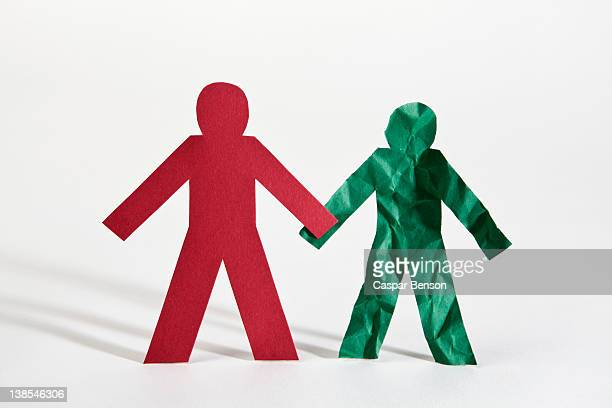 Two paper dolls holding hands, one crumpled