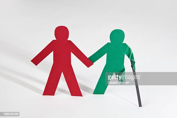 Two paper dolls holding hands, one with an injury
