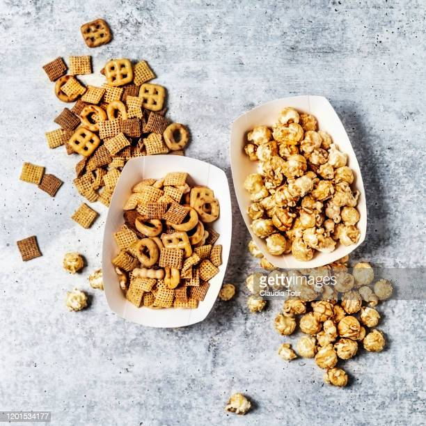 two paper trays with caramelized popcorn and snack mix on gray background - salted stock pictures, royalty-free photos & images