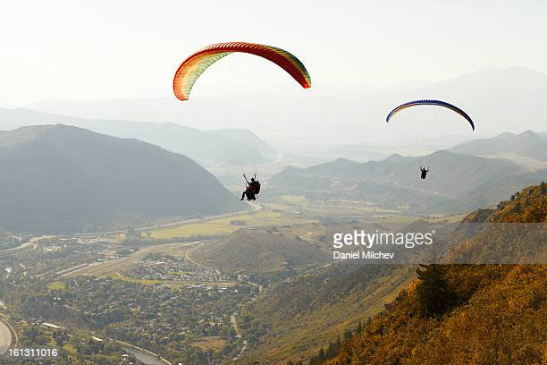 Two paragliders flying over a valley.