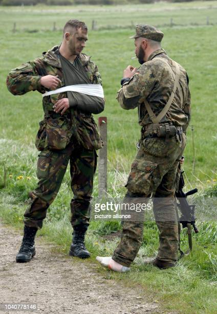Two paratroopers in conversation after injuring themselves during a jump out of a Transall transport plane over Ahrenvioelfeld Germany 10 May 2017...