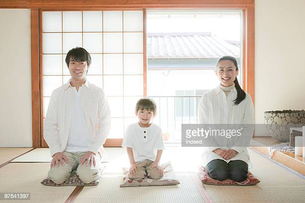 Two parents and son kneeling on cushions, smiling