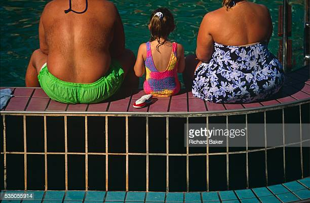 Two parents and their daughter sit with their backs to the viewer on the edge of a pool on the open deck of the Fun Ship Ecstasy belonging to...