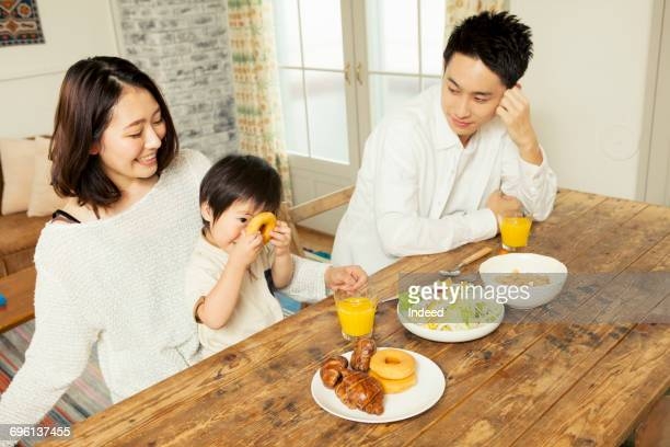 Two Parents eating food with their son on table
