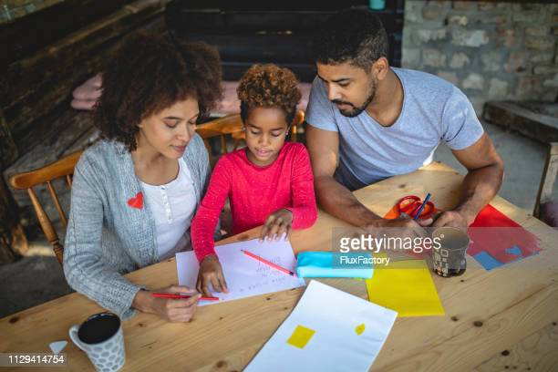 two parents helping their daughter with homework - craft stock pictures, royalty-free photos & images