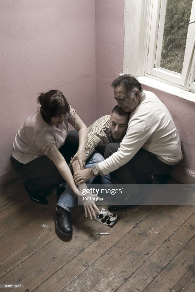 Two Parents Hold Young Man's Arm From Reaching Syringe : Stock Photo