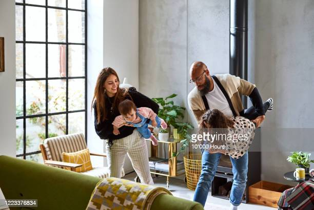 two parents playing with daughters at home - daughter stock pictures, royalty-free photos & images