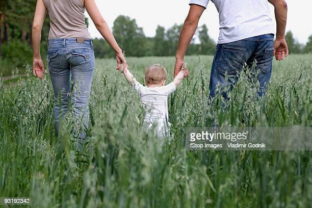 Two parents walking in a field with their daughter