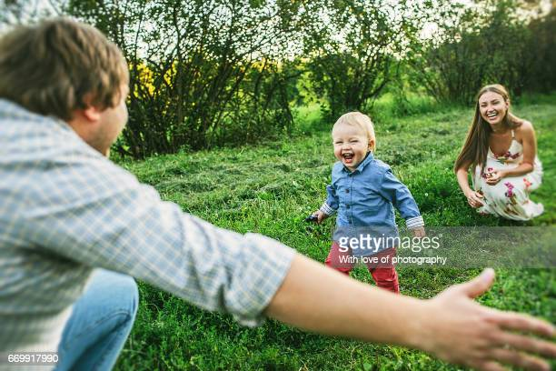 two parents with little toddler son 1 year old playing outdoors on a sunny day in countryside on green grass