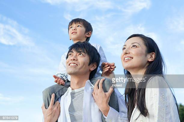 two parents with son looking up, low angle view - japan mom and son stock photos and pictures