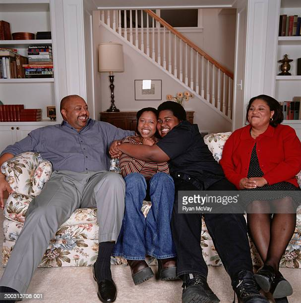 two parents with teenage son and daughter (16-17), sitting on sofa in living room, portrait - fat woman sitting on man stock pictures, royalty-free photos & images