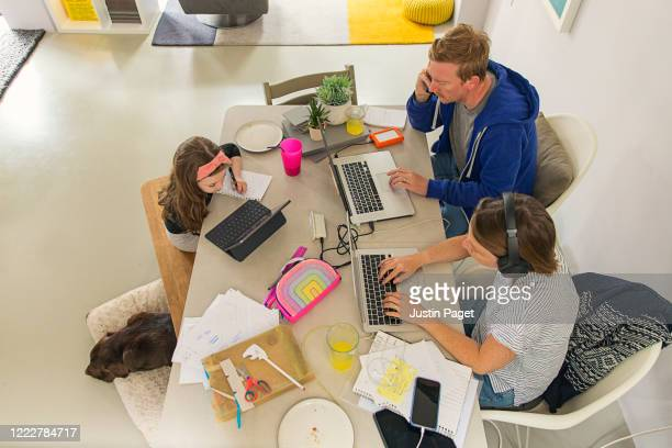two parents working from home whilst their daughter remote schools - ホームスクーリング ストックフォトと画像
