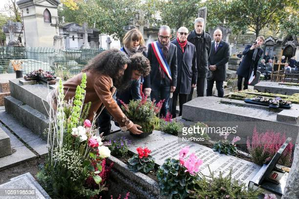 Two Parisian students lay flowers at the grave of French poet Guillaume Apollinaire in Père Lachaise Cemetery in Paris on Novembre 8 during the...