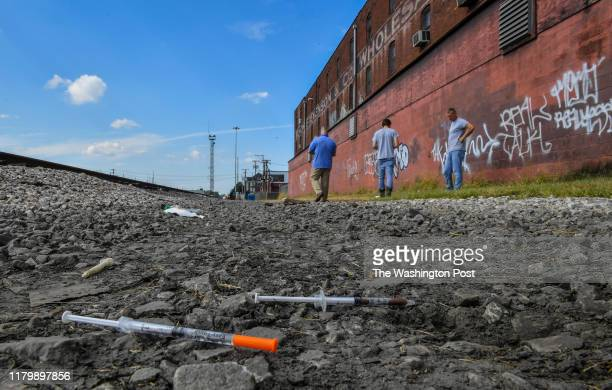 Two partially used syringes and needles are seen as Rocky Meadows, left, former addict and founder of Lifehouse treatment and recovery center, walks...