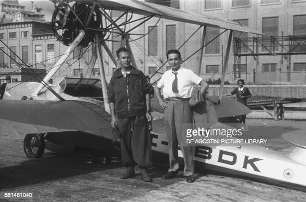 Two participants at the RUNA air show in front of a seaplane June 29 seaplane base in Genoa Italy 20th century
