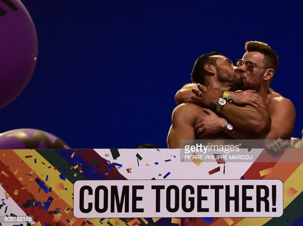 TOPSHOT Two participants kiss eachother as they ride on a float during the WorldPride 2017 parade in Madrid on July 1 2017 Revellers took to the...
