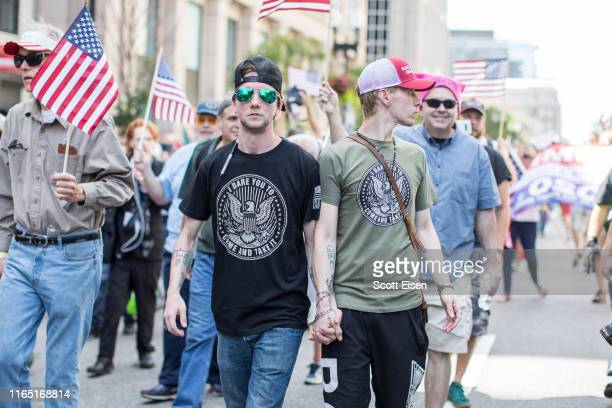 Two participants of the Boston Straight Pride Parade hold hands on August 31 2019 in Boston Massachusetts The organization Super Happy Fun America...