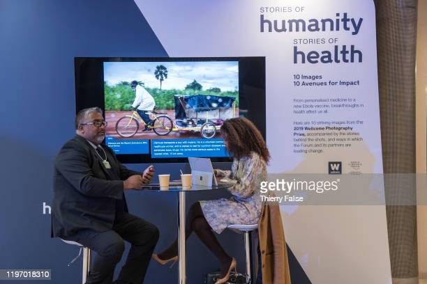 Two participants sit in front of a screen showing pictures on health issues at the 50th World Economic Forum in Davos