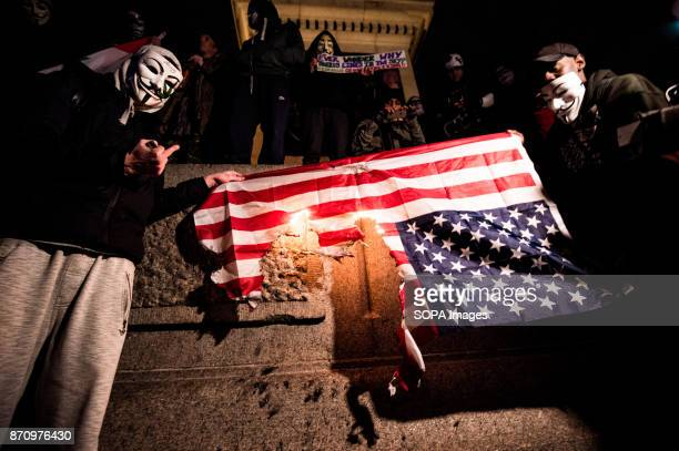 Two participants with Guy Fawkes masks seen setting the United States flag on fire Demonstrators attend the Annual Million Mask March bonfire night...